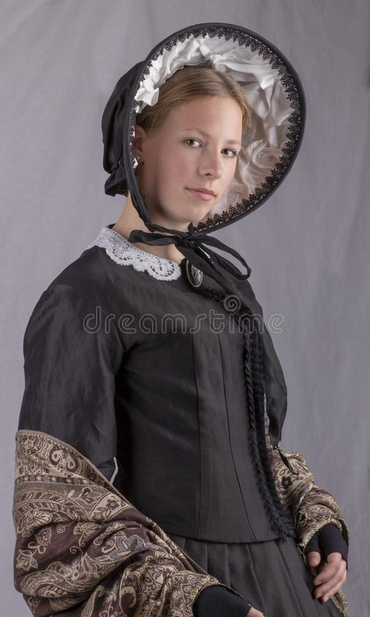 Victorian woman in a black bodice, shawl and bonnet. On a studio backdrop stock photos