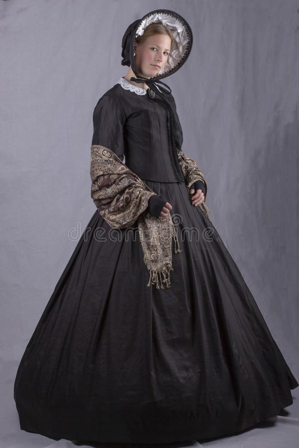 Victorian woman in a black bodice, shawl and bonnet. On a studio backdrop royalty free stock image