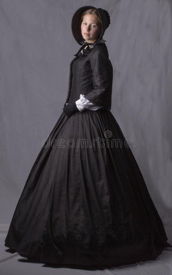 Victorian woman in a black bodice, skirt and bonnet. On a studio backdrop royalty free stock image