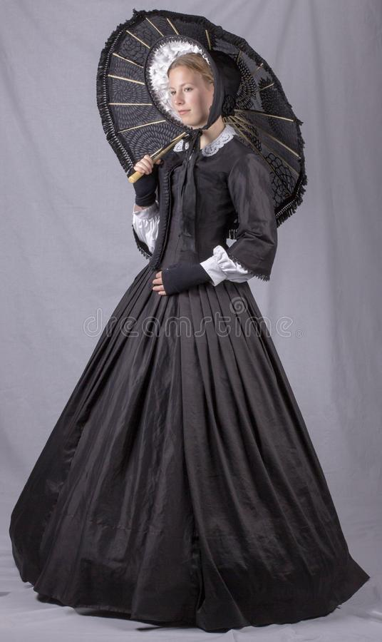 Victorian woman in a black bodice, skirt, parasol and bonnet. Victorian woman in a black bodice, skirt and bonnet holding a parasol on a studio backdrop stock photography