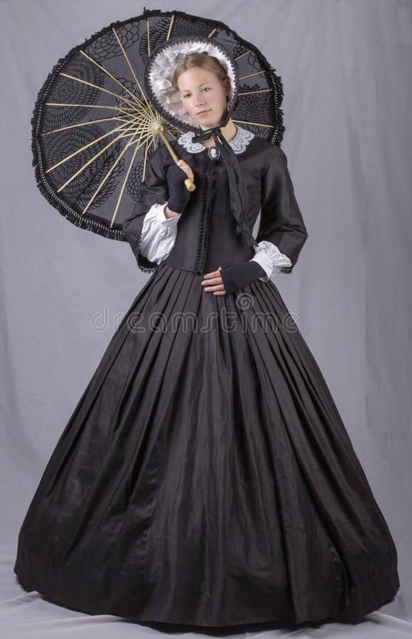 Victorian woman in a black bodice, skirt, parasol and bonnet. Victorian woman in a black bodice, skirt and bonnet holding a parasol on a studio backdrop stock photos