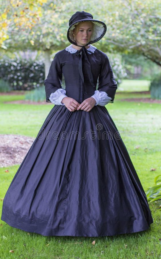 Victorian woman in black dress walks in a summer garden stock images
