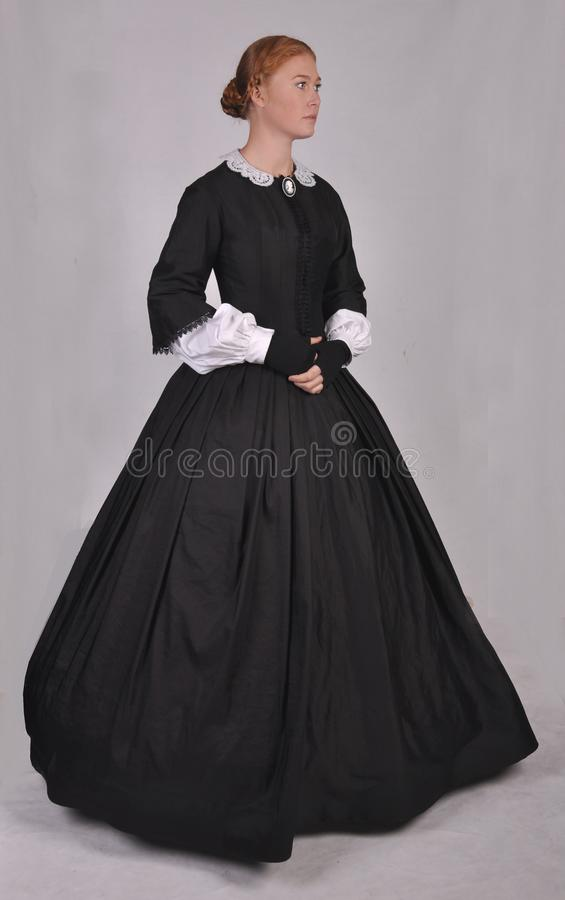 Victorian woman in black ensemble  on studio backdrop royalty free stock images