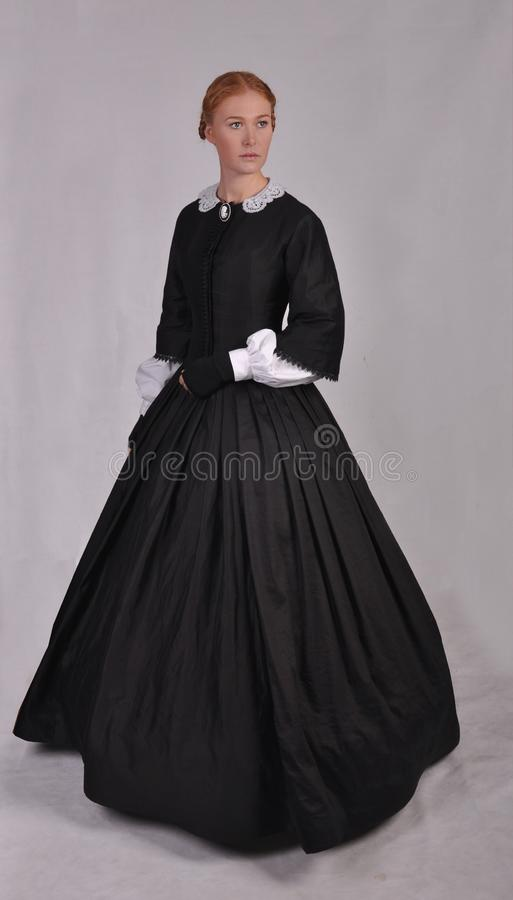 Victorian woman in black ensemble  on studio backdrop stock images