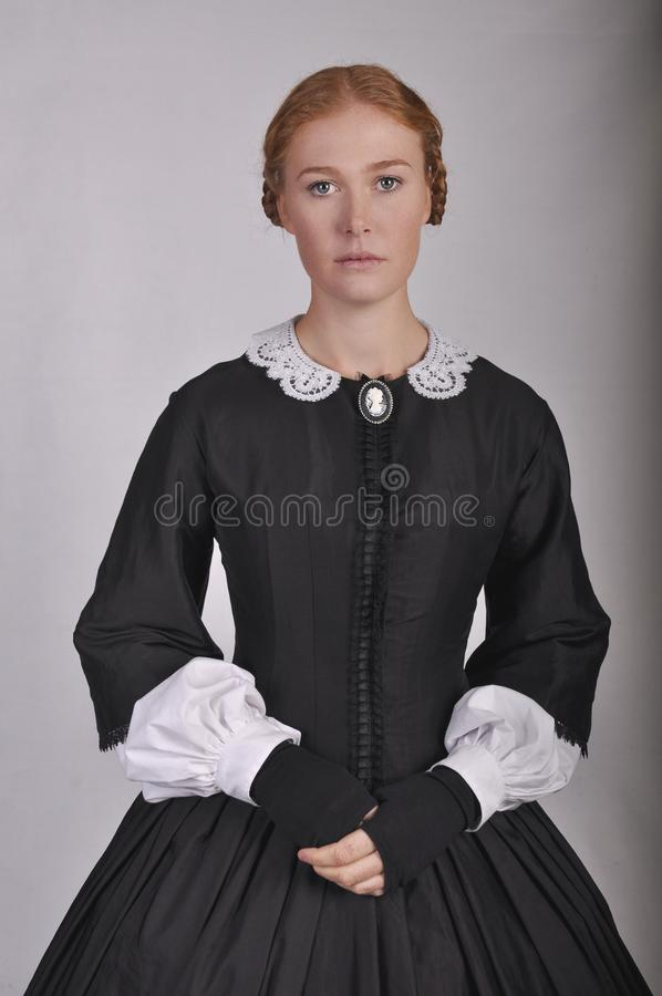Victorian woman in black ensemble  on studio backdrop royalty free stock photo