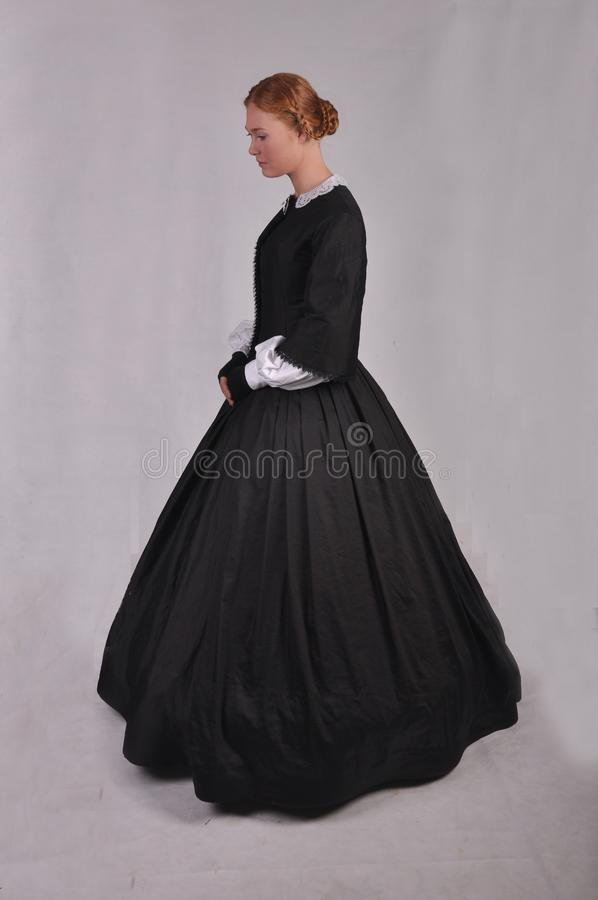 Victorian woman in black ensemble  on studio backdrop royalty free stock image