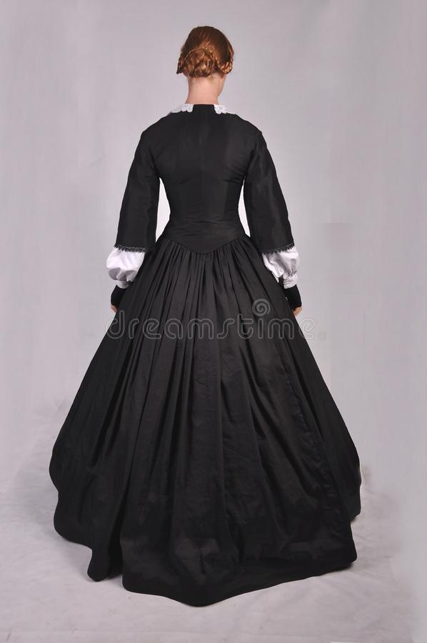 Victorian woman in black ensemble  on studio backdrop royalty free stock photography
