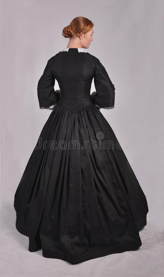 Victorian woman in black ensemble  on studio backdrop stock photography