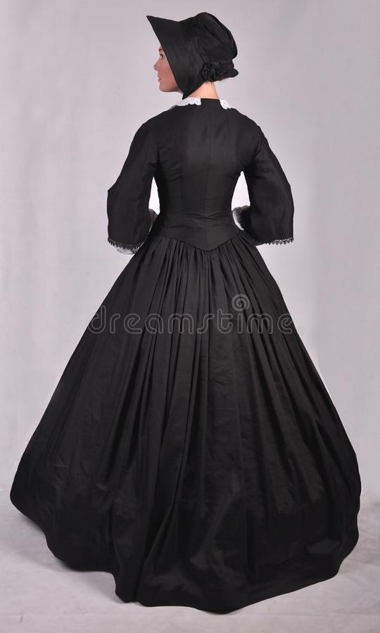 Victorian woman in black ensemble  on studio backdrop stock image