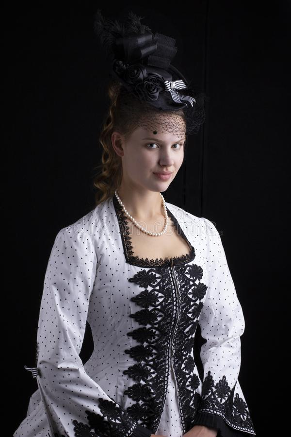 Victorian woman in black and white bustle dress and hat. Victorian woman wearing an 1870`s black and white bustle dress and hat with a veil on a black background stock image