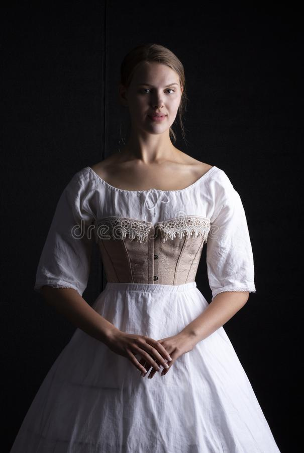 Victorian woman in underwear. Victorian woman in chemise, corset and crinoline on a black background stock photos