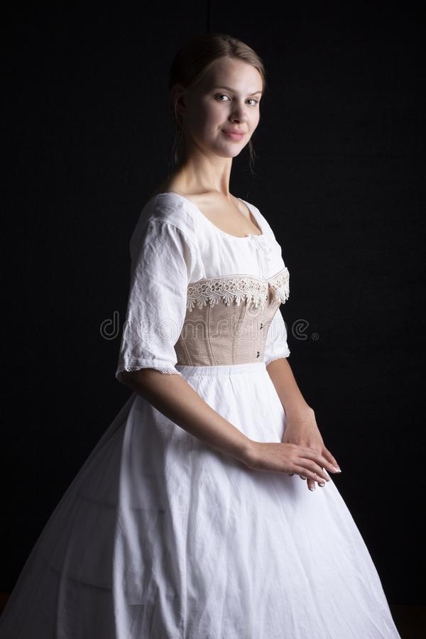 Victorian woman in underwear. Victorian woman in chemise, corset and crinoline on a black background royalty free stock photos