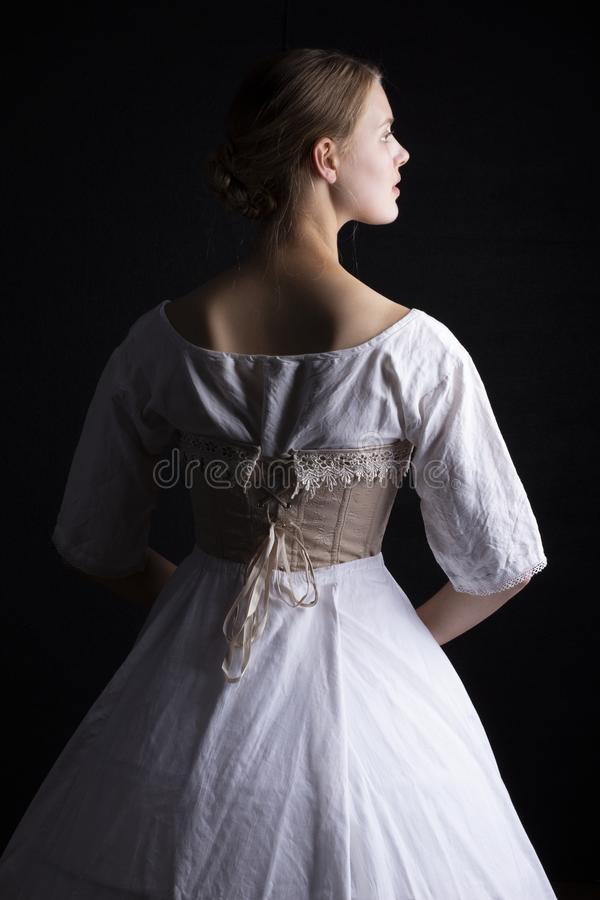 Victorian woman in underwear. Victorian woman in chemise, corset and crinoline on a black background royalty free stock images