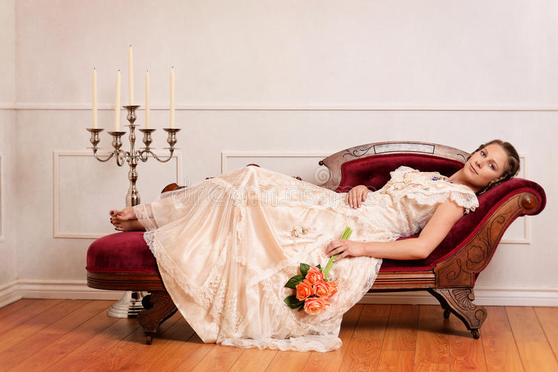 Victorian woman on couch with orange roses. Portrait of victorian woman on couch with orange roses stock images