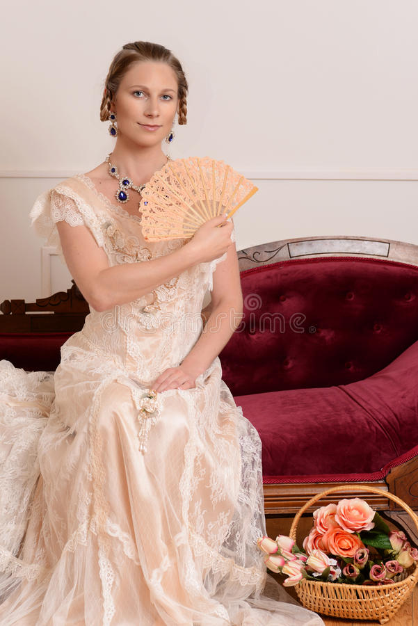 Victorian woman with fan on fainting couch. Portrait of victorian woman with fan on fainting couch royalty free stock images