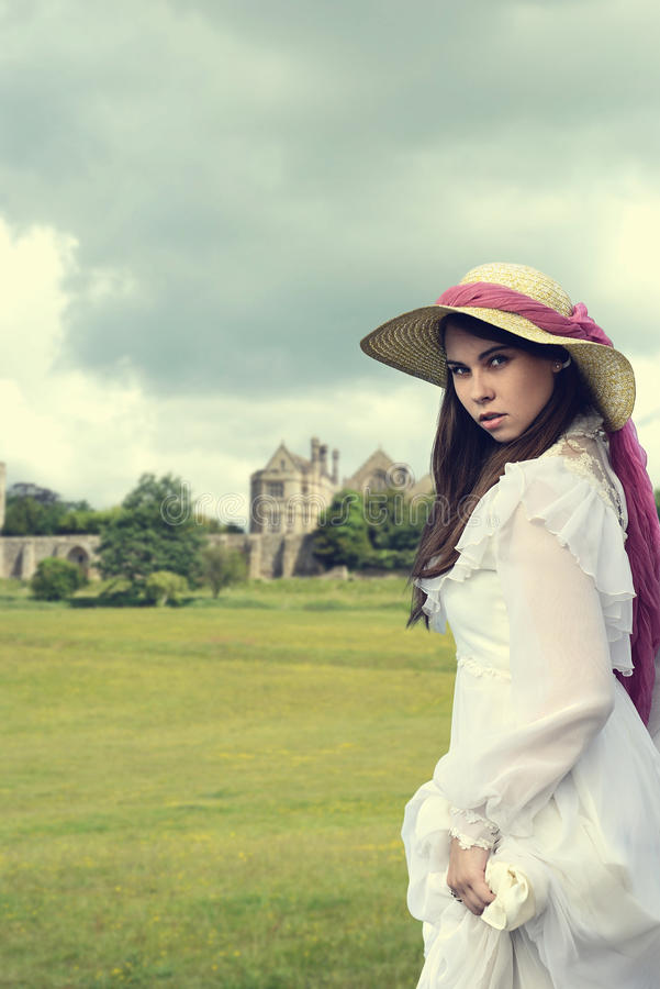 Victorian woman with manor house. Young victorian woman with manor house royalty free stock image