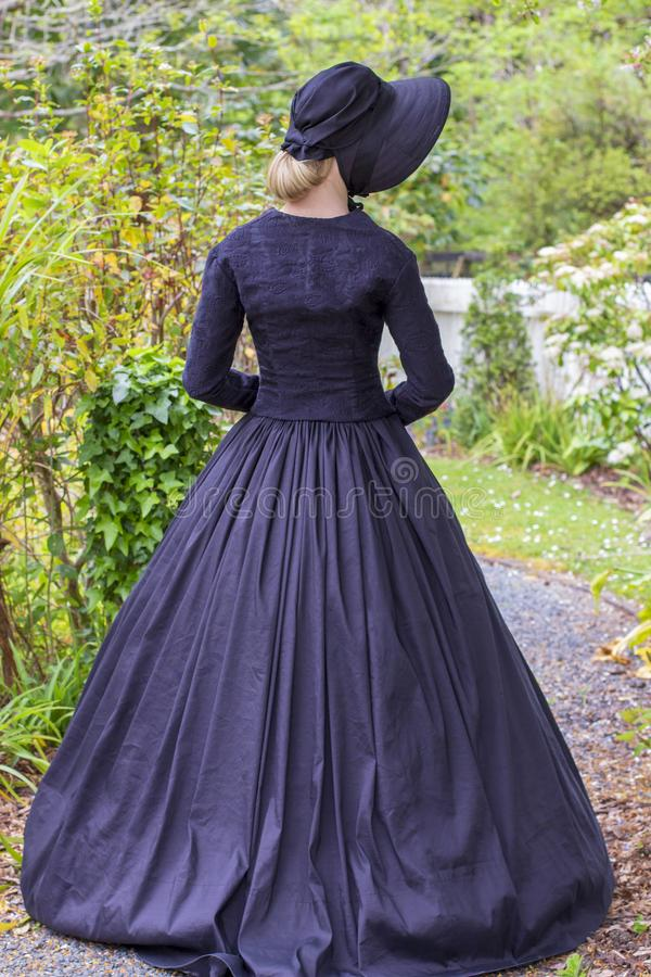 Victorian woman in summer garden. Mid-Victorian woman in a black ensemble and bonnet walking in a summer garden royalty free stock image