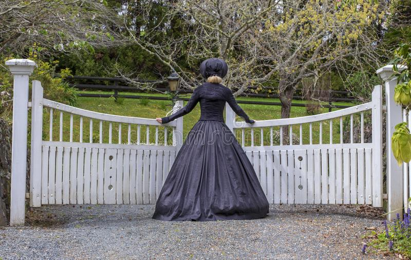 Victorian woman in summer garden and opening a gate royalty free stock photos