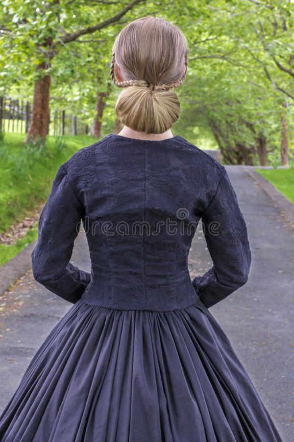Victorian woman in summer garden walking under trees on a paved road. Mid-Victorian woman in a black ensemble and bonnet walking under trees on a paved road in a stock photography