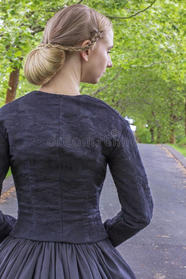 Victorian woman in summer garden walking under trees on a paved road. Mid-Victorian woman in a black ensemble and bonnet walking under trees on a paved road in a stock image