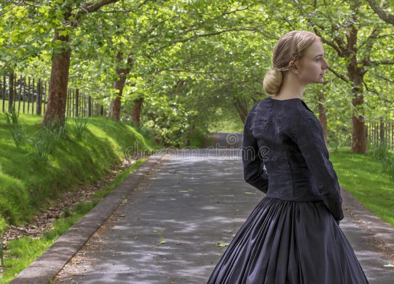 Victorian woman in summer garden walking under trees on a paved road. Mid-Victorian woman in a black ensemble and bonnet walking under trees on a paved road in a royalty free stock photo