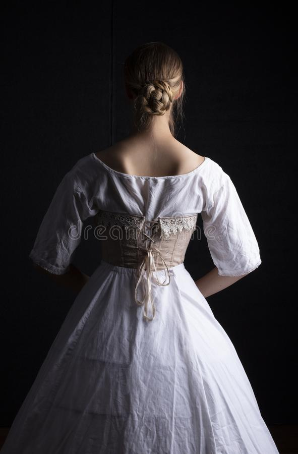Victorian woman in underwear. Victorian woman in chemise, corset and crinoline on a black background stock photo