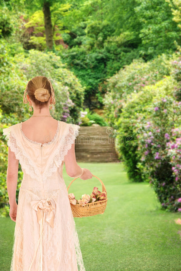 Victorian woman walking in garden with roses. Portrait of victorian woman walking in garden with roses walking in her garden royalty free stock photos