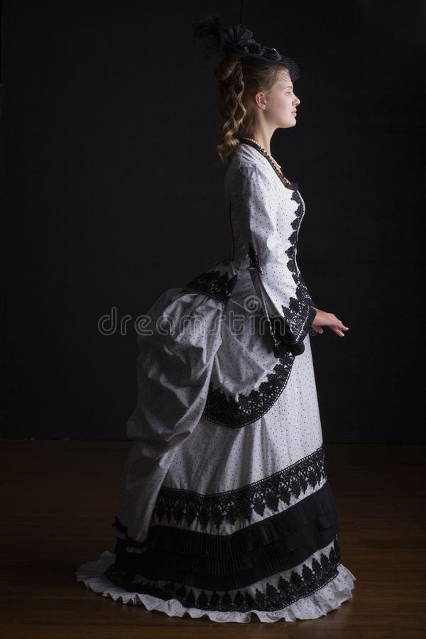 Victorian woman in black and white bustle dress and hat. Victorian woman wearing an 1870`s black and white bustle dress and hat with a veil on a black background stock images