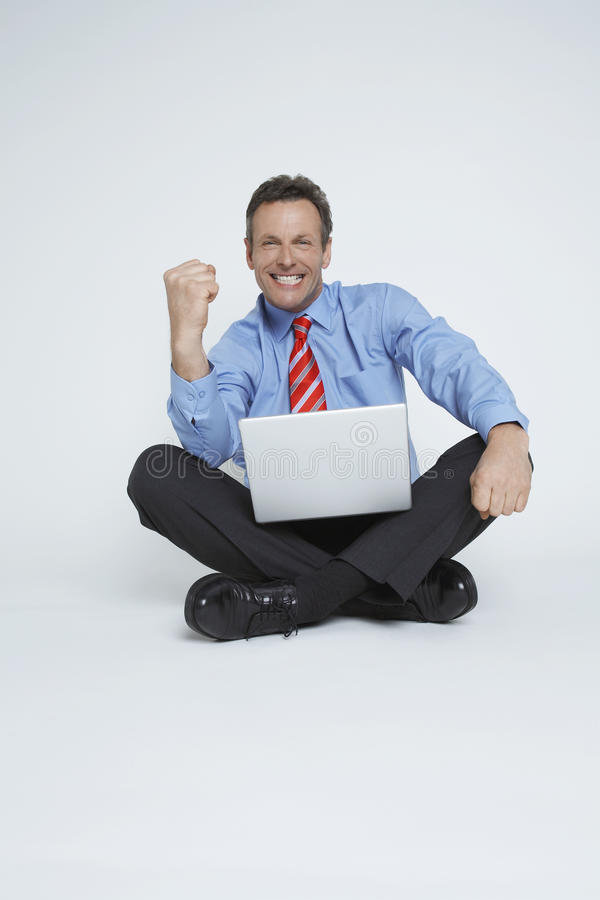 Victorious Businessman With Laptop stock photo