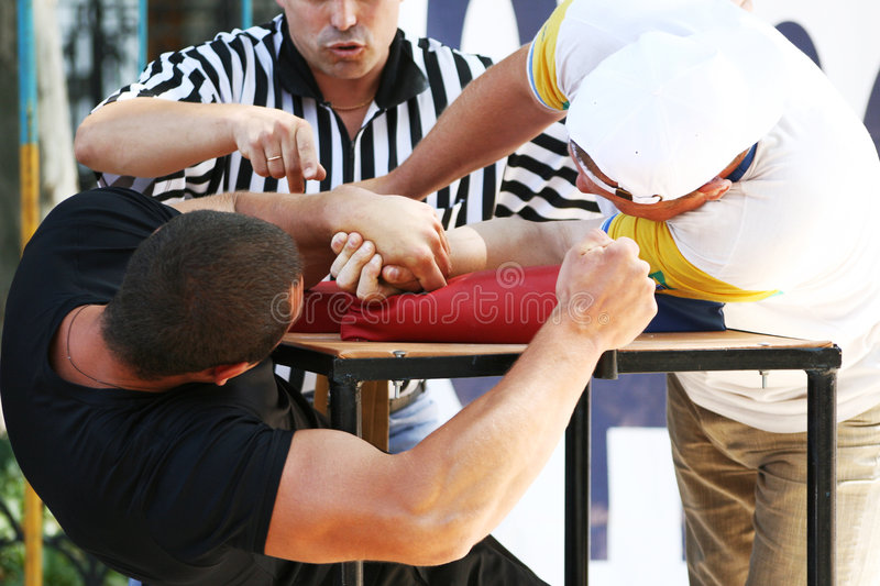 Victorious duel on armwrestling. The referee has fixed a victory in a duel on armwrestling royalty free stock photos