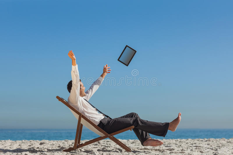 Victorious young businessman on his deck chair throwing his tablet away royalty free stock photography