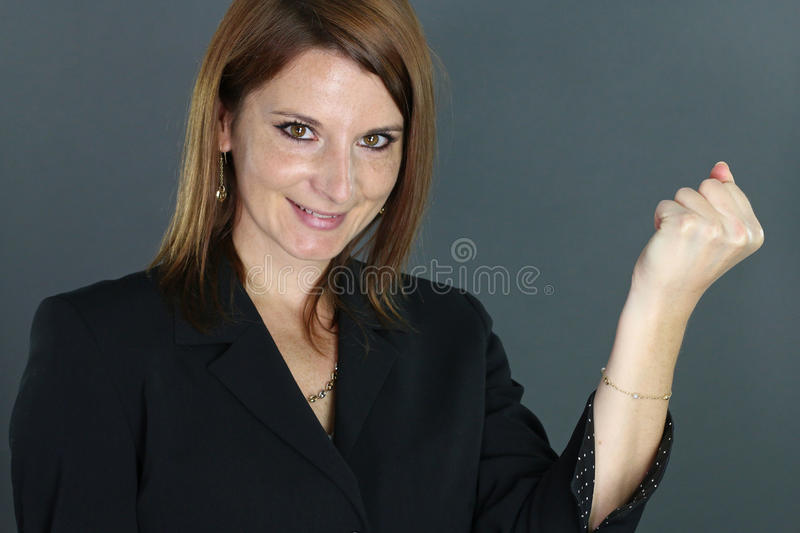 Victorious young woman. Over a gray background royalty free stock photography
