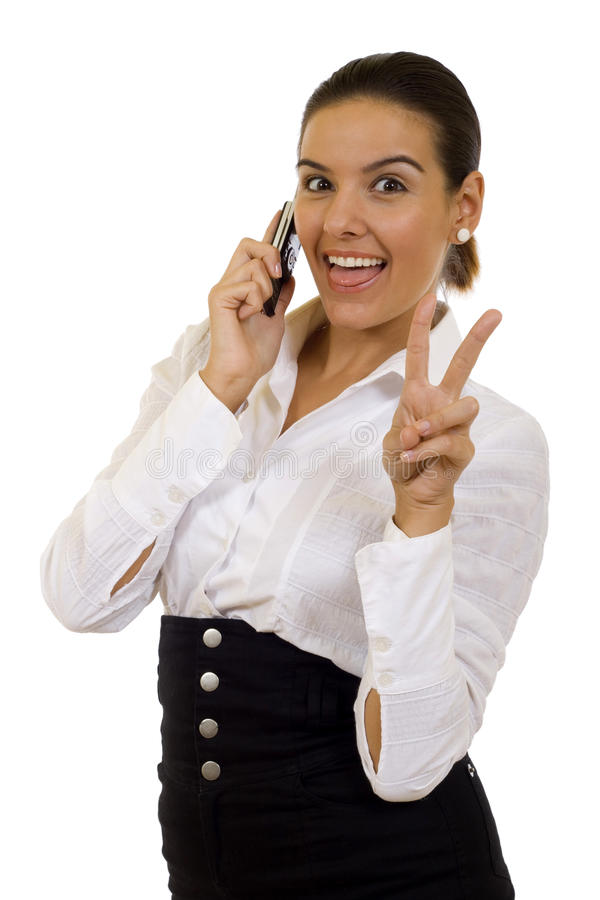 Victory!. Happy businesswoman with phone and victory gesture, isolated stock photo