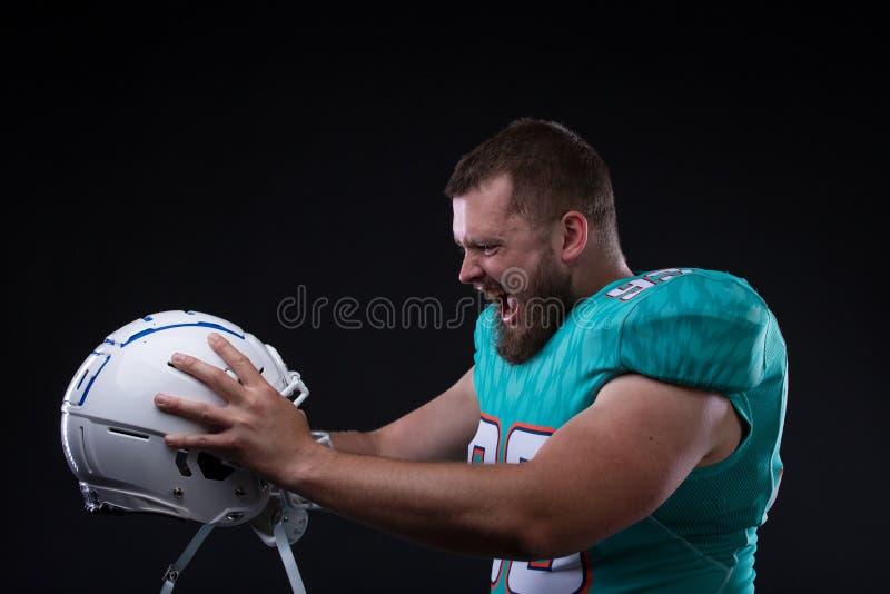 Victory Agressive American-voetbalster die bij de helm gillen terwijl status tegen zwarte achtergrond royalty-vrije stock foto's