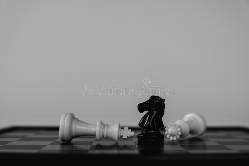 Victory of chess knight, stand over fallen king and queen. The winner in business competition. Competitiveness and strategy. Leader, courage, success, brave royalty free stock image