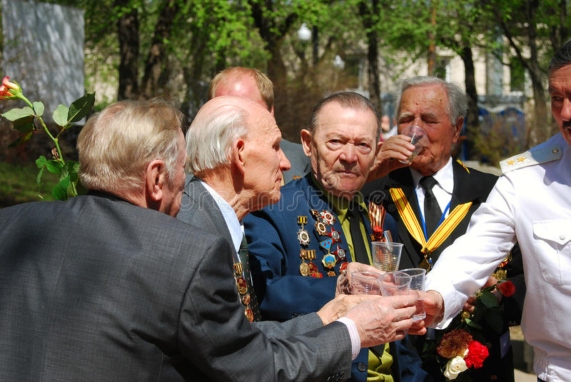 Victory Day celebration in Moscow. War veterans group. MOSCOW, RUSSIA - MAY 09: War veterans group. One of them looks at camera. They hold glasses with drinks royalty free stock photo