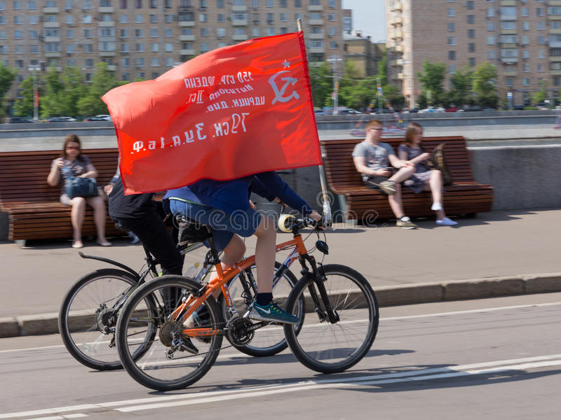 Victory Day in Gorky Park, Moscow. Moscow - May 9, 2016: People on bikes carry the Banner of Victory, which is picked up on the roof of the Reichstag building in royalty free stock photography
