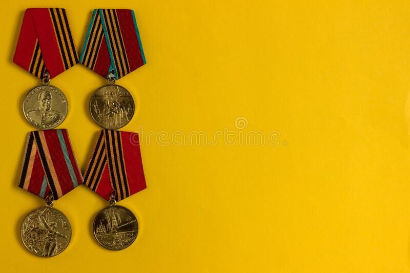 Victory Day May 9, background. Many medals of the Second World War lie on a yellow background.  royalty free stock photography