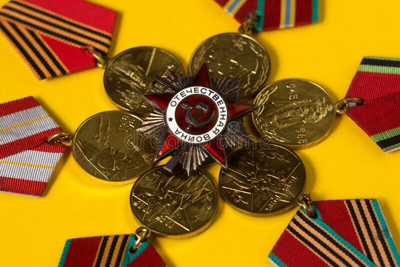 Victory Day May 9, background. Many medals of the Second World War lie on a yellow background.  stock images