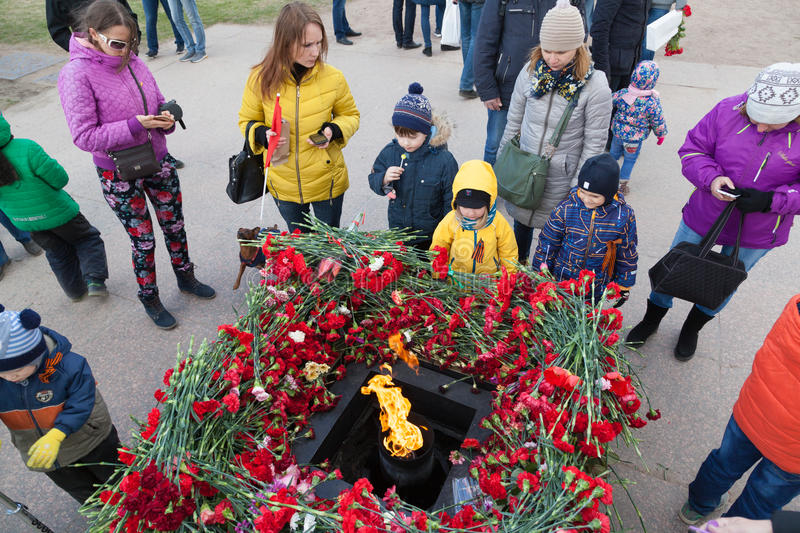 Victory day in St. Peterburg. ST. PETERSBURG, RUSSIA - MAY 9, 2017: Laying flowers at the eternal fire on the Field of Mars Marsovo Polye on celebration of 72 stock photo
