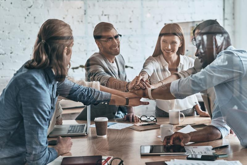 Victory! Diverse group of business colleagues holding hands on stock photos