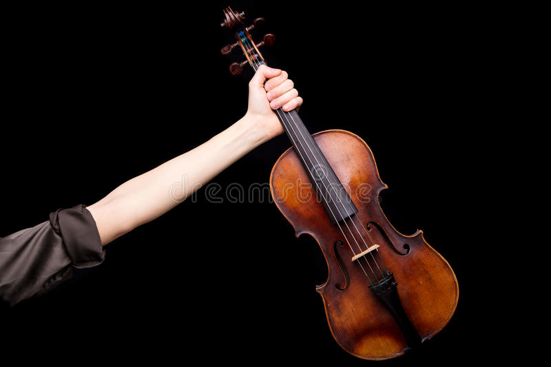 Until the victory my brave violin. Right arm of a female violin player rising out and holding an handcrafted violin on a black background with lots of copyspace royalty free stock images