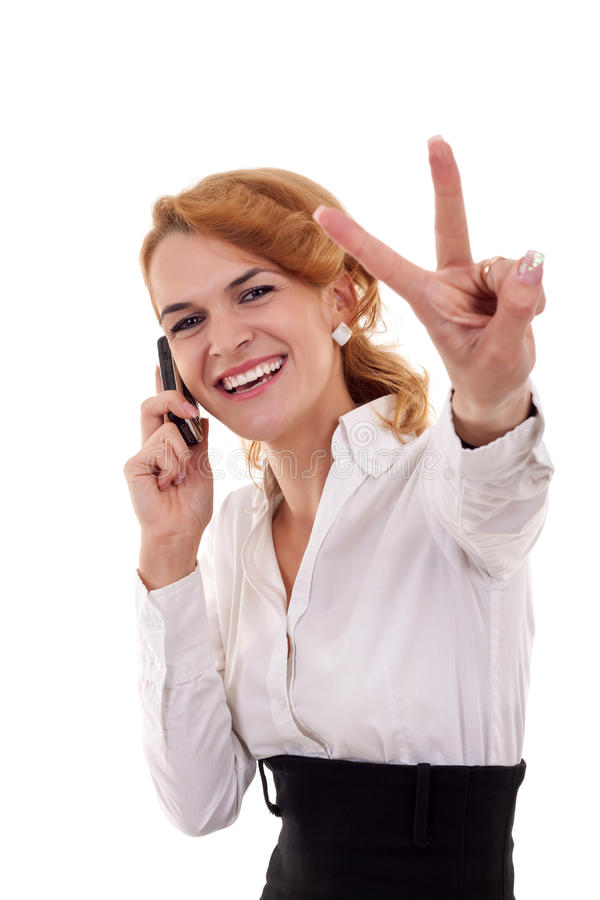 Victory on the phone. Happy business woman with phone and victory gesture, isolated stock image