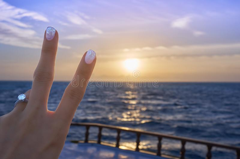 Victory posed woman`s hand with diamond ring and nail art during sunset. Victory posed woman`s hand with diamond ring and nail art on a ship in Maldives ocean stock image
