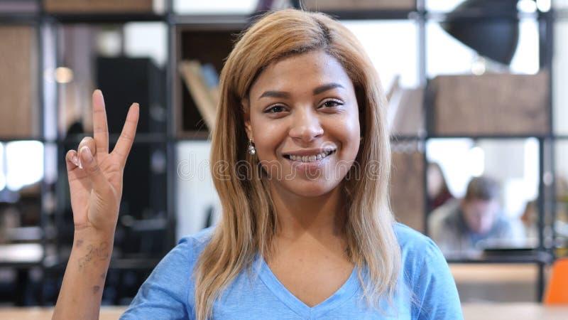 Victory Sign par la jeune femme afro-américaine, portrait photographie stock