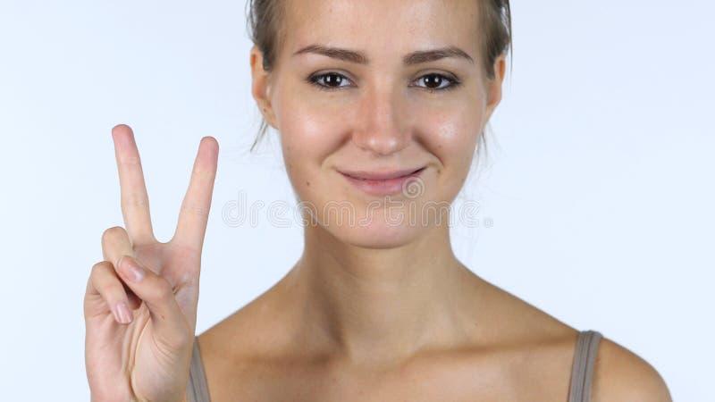 Victory Sign slut upp av den lyckade härliga flickan, vit bakgrund arkivfoto