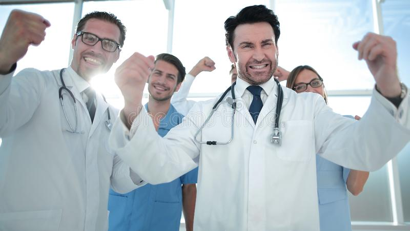 A victory sign of a team of doctors in white coats royalty free stock photography