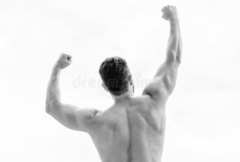 Victory and success. Champion and winner concept. Man celebrating success. Bodybuilder strong muscular body feeling. Powerful and superior rear view. Achieve stock photos