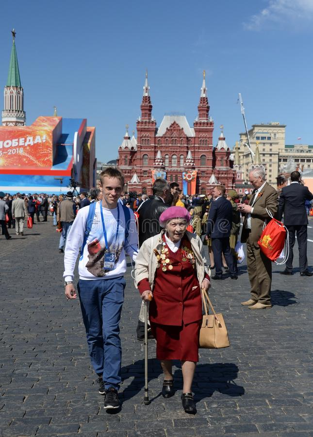 Victory Volunteer ayuda a una mujer del veterano en Plaza Roja en Moscú fotos de archivo