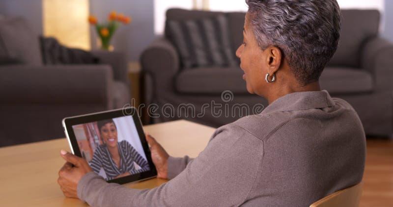 Vidéo africaine de grand-maman causant sur le comprimé images libres de droits